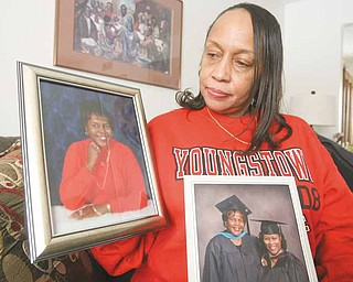 Davida Brown of Youngstown, a daughter of slain real estate broker Vivian Martin, wants the suspects charged in her mother's death tried here. She is shown with a photo of her mother and a graduation photo of her mother and her sister, Donna James. In 2005, Martin received her master's degree in organizational leadership from Geneva College, Geneva, Pa., and James received her master's degree in business administration from Youngstown State University, where she is a payroll specialist.