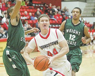 Youngstown State's Vytas Sulskis (44) drives through Wright State defenders N'Gai Evans, left, and Armand Battle (12) during the first half of Thursday's game at YSU's Beeghly Center. The Penguins kept it close, but fell to the Raiders, 66-62.