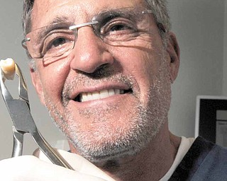 Miami Beach oral surgeon Dr. Jeffrey Blum holds a molar similar to the one that would be sent to a cryogenics lab in New York City where it would be frozen and stored.