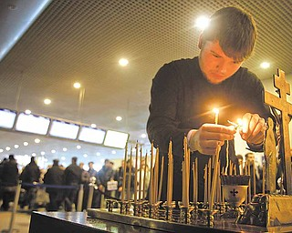 A clergyman lights candles at a site of a blast at Domodedovo airport near Moscow on Wednesday, Jan. 26, 2011. Security was tightened in Moscow on Tuesday, after a suicide bomber set off an explosion that ripped through Moscow's busiest airport on Monday.