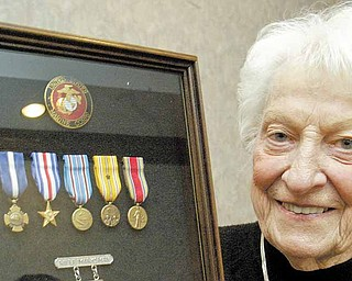 Suzanne Johnson McLaughlin holds  a display of her late husband Charles Johnson's war medal. He was posthumously awarded the Navy Cross.