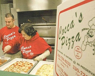 William D. Lewis|The Vindicator  SteveCocca and his mother Tina Cocca whose family owns Cocca's Pizza at work in thier New Middletown pizzaria.