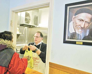 St. Vincent DePaul Society Dining Manager Skip Barone hands out a lunch at the Front Street, Youngstown location. A portrait of St. Vincent DePaul hangs on wall at right.