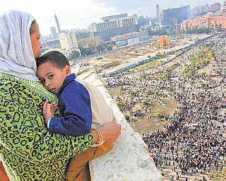 An Egyptian mother hugs her child as she watches some thousands of Egyptian protesters gather at Tahrir square in Cairo, Egypt, Sunday, Jan. 30, 2011, with the ruling National Democratic party building burned at top right behind the red coloured Egypt museum. The army sent hundreds more troops and armored vehicles onto the streets of Cairo and other cities but appeared to be taking little action against mass protests on Sunday.