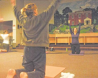 Jennifer Neal, background right, leads a yoga class in a stretching exercise at Liberty Township Administration Building, 1315 Church Hill-Hubbard Road. Sessions are at 7 p.m. Sundays. The other two women are unidentified. Candles and music of singing bowls and healing bells set the mood for an evening to uplift the body and soul.