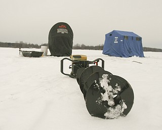 ROBERT K. YOSAY | THE VINDICATOR..Ice Fishing is cool - A power auger for cutting through the ice sits dormant outside two ice shelters on Mosquito Lake ... Ó--30-..