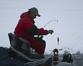 ROBERT K. YOSAY | THE VINDICATOR..Ice Fishing is cool - fresh catch as John Walczak of Campbell pulls out a crappie from Mosquito Lake . Aids such as lanterns, ice  houses, heaters, fishfinders are common.... Ó--30-..