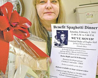 Cindy Michael, who founded the Lena, Mason, Christian Foundation to remember the three murder victims, holds a flyer for a benefit spaghetti dinner on Saturday that will feature a basket raffle. The dinner funds projects that help children.