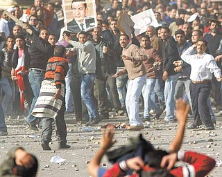 Pro-government supporters, top, clash anti-government protestors in Cairo's main square, Egypt, Wednesday, Feb.2, 2011. Several thousand supporters of President Hosni Mubarak, including some riding horses and camels and wielding whips, clashed with anti-government protesters Wednesday as Egypt's upheaval took a dangerous new turn.