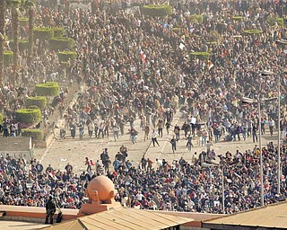 Pro-government demonstrators, below, clash with anti-government demonstrators, above, as an Egyptian Army soldier on the rooftop of the Egyptian Museum observes the scene in Tahrir square, the center of anti-government demonstrations, in Cairo, Egypt Wednesday, Feb. 2, 2011.