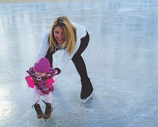 Laura Glass helps 4-month-old Alexis Spagnoletta of Girard at the ice rink Laura and her husband, Rick, built on their property in McDonald.