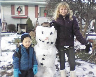 Timmy, 4, and Kayla, 14, both of Poland, proudly show off their snowman. Photo sent in by Gary Kerr.