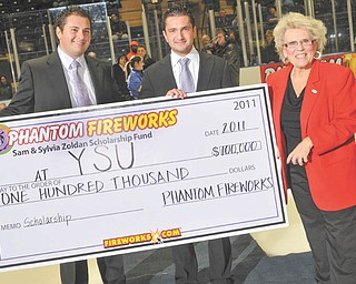 Sky's the limit with education: Dr. Cynthia Anderson, right, president of Youngstown State University, accepts a check for $100,000 from Phantom Fireworks at a Youngstown Phantoms Hockey game. The check was presented Jan. 29 by Phantoms Hockey president and vice president, Alex Zoldan, left, and Ron Zoldan. The money is for YSU's Sam and Sylvia Zoldan Scholarship Fund, established in memory of Alex and Ron's grandparents, the parents of Phantom Fireworks President Bruce J. Zoldan and Vice President Alan L. Zoldan.