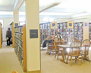 Main Library patrons look through stacks and read at a study area inside the facility. An architectural study recommends $11 million worth of improvements to the library.