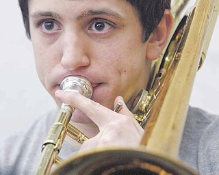 Boardman High School 12th grade band member Tony Colella plays trombone during practice. Celella is one of 275 musicians in the Marching Band who have split up into other bands and ensembles for the winter season.