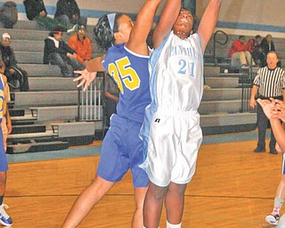 (21) Ashlyn Baker of East is fouled by (35) Monet Saunders during thier game Monday night in Youngstown.