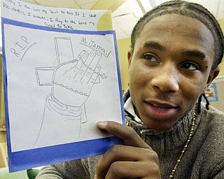 Wilson Middle School eighth grader Lynell Lockhart holds a card he made in memory of the late Jamail Johnson who was a math tutor at Wilson.