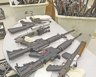The 232 weapons in three large rolling bins and four milk crates were on display at the Cleveland Police headquarters confiscated from Abbot John Henry of St. Herman's House of Hospitality in Cleveland February 8, 2011.  Investigators with Henry's consent  rounded up 80 guns with ammunition from a home near St. Herman's. On Friday, another 150 guns and ammunition were recovered from a Trumbull County farm the shelter owns.