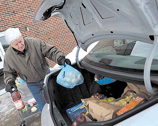 Volunteer Mel Petefish of Liberty, loads a car full of donated food from Share Outreach program Wednesday afternoon. The program runs out of the Pleasant Valley Church in Niles once a week and provides food and clothing to those in need.