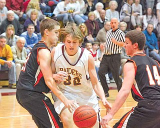 South Range junior Jordan Baker tries to maintain possession of the ball while his guarded by (14) Brad Ferraro and (31) Ron Rogers.