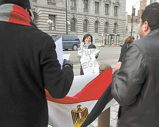 Salam Elwanni of Youngstown holds a sign referring to the recent revolutions in Tunisia and Egypt and speculating on which country could protest for its freedom next. She was among about 40 demonstrators celebrating the departure of Hosni Mubarak as Egypt's president at a downtown Youngstown rally Friday in front of the Lambros Federal Building and U.S. Courthouse on Market Street. In the background is the Mahoning County Courthouse.