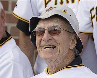 FILE - In this June 30, 2009, file photo, former Pittsburgh Pirates manager Chuck Tanner smiles during a photo next to a replica of the outfield wall at Forbes Field on display at PNC Park in Pittsburgh. Tanner, who managed the Pirates to one of the greatest comebacks in World Series history, died Friday, Feb. 11, 2011, at his home in New Castle, Pa., after a long illness, the team Pirates said. He was 81. (AP Photo/Gene J. Puskar, File)