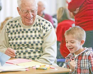 Aidan Hankey, right, and William Ronci from Shepherd of The Valley-Poland and a World War II Army veteran, share a laugh while making Valentine's Day cards to be sent to military personnel in Afghanistan. Aidan is a kindergarten student at Zion Christian School at Zion Lutheran Church in Youngstown. Ronci fought in several battles with the 3rd and 7th Armies in their drive across Europe toward Germany. A group of young veterans, members of the Armed Forces Student Association at Youngstown State University, also participated in the event sponsored by Shepherd of the Valley Home Health.