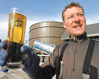In this Jan. 26, 2011 photo, Eric Fitch holds a Magic Hat glass in front of the digester building at the brewery in South Burlington, Vt.  The Vermont brewery is giving new meaning to the idea of green beer. Magic Hat Brewing Co., of South Burlington, is the first site to use a device that turns spent grain from the brewing process into natural gas that is then used to fuel brewing operations.  The 42-foot tall anaerobic methane digester, installed last summer, extracts energy from the spent hops, barley and yeast left over from the brewing process.
