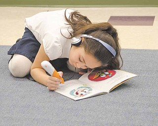 Makenna Ploessel, 6, uses a Leapfrog electronic pen and headphones to make her way through a book, using both audible and visual cues to learn. Makenna is in kindergarten in Jessica Redmond's class at Taft Elementary School in Youngstown. The device is one of the educational materials Redmond received after collecting donations online through DonorsChoose.org. The website allows teachers to post the projects or materials they're requesting and allows people to contribute to them.