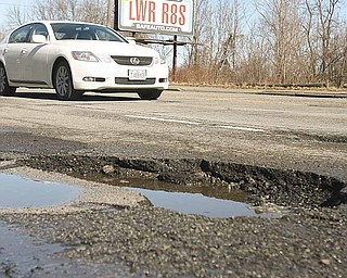 Potholes such as this one in the 1400 block of South Avenue are easy to spot during the day but can be masked in puddles and during night travel. They can cause damage a vehicle's tires, alignment and suspension.