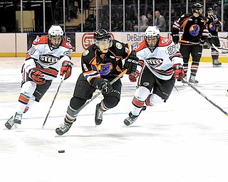 Youngstown Phantom Andrew Sinelli chases the puck down the ice while being pursued by the Chicago Steel's Jimmy Devito (20) and Peter Hand (27) .