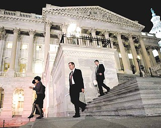 Congressmen walk down the steps of the House of Representatives as they work throughout the night on a spending bill, on Capitol Hill in Washington, Friday, Feb. 18, 2011