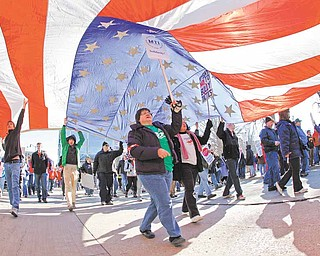 "AFSCME memeber Merryann Wen of Delevan, Wis., help holds up an American Flag as she marches around the the State Square in Madison, Wis., Saturday, Feb. 19, 2011.  A few dozen police officers stood between supporters of Republican Gov. Scott Walker on the muddy east lawn of the Capitol and the much larger group of pro-labor demonstrators who surrounded them.   The protest was peaceful as both sides exchanged chants of ""Pass the bill! Pass the bill!"" and ""Kill the bill! Kill the bill!""  The Wisconsin governor, elected in November's GOP wave that also gave control of the state Assembly and Senate to Republicans, set off the protests earlier this week by pushing ahead with a measure that would require government workers to contribute more to their health care and pension costs and largely eliminate their collective bargaining rights."
