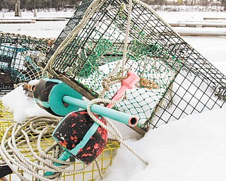 In this Feb. 16, 2011 photo, snow covered lobster traps and gear are seen on a dock in Freeport,  Maine.  A lawmaker has introduced a bill this legislative session that makes it legal for traps to be stored on wharfs year round.