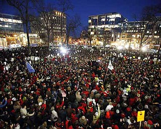 The Rev. Jesse Jackson, near right center of photo, takes the stage amidst tens of thousands of protesters gathered at the State Capitol in Madison, Wis., Friday,  Feb. 18, 2011.