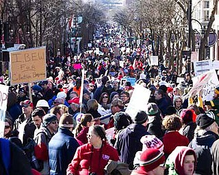 "Protesters gather down State Street in Madison, Wis.  after a  a rally outside  the Wisconsin State Capitol  on  Saturday, Feb.  19, 2011.   A few dozen police officers stood between supporters of GOP Gov. Scott Walker on the muddy east lawn of the Capitol and the much larger group of pro-labor demonstrators who surrounded them. The protest was peaceful as both sides exchanged chants of ""Pass the bill! Pass the bill!"" and ""Kill the bill! Kill the bill!"" (AP Photo/Wisconsin State Journal, Steve Apps)"