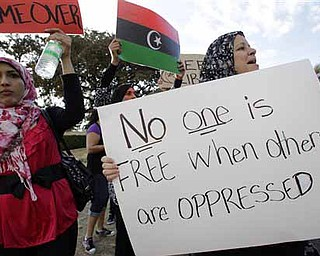 Libyan-American citizen Jamila Rashed, right, of Denton, Texas, holds a sign as she joins nearly 200 others during a rally at Dealey Plaza, Sunday, Feb. 20, 2011, in Dallas. Rashed said that she responded to a message on a social network site that called for the rally at the downtown Dallas plaza in support of a freedom in the country of Libya.