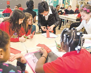 Visiting Chinese educator Nancy Zhang demonstrates the traditional art of Chinese paper-cutting in a fourth-grade classroom Tuesday morning at Campbell Elementary School. Zhang and fellow educator Judy Teng arrived here Feb. 4 and will go back to China Friday.
