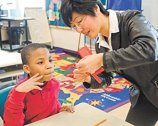 Jordan Weatherly, 9, gets personal instruction from Nancy Zhang during the Chinese paper-cutting lesson.