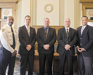 Youngstown Police Chief Jimmy F. Hughes, from left, newly-promoted city police officers Lt. Jason Simon, Lt. William Ross and Capt. Mark Milstead, and Mayor Jay Williams stand together in city council chambers. The three were sworn in to their new positions during a ceremony Tuesday.
