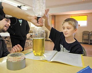 Mason Harding, 11, a fifth-grade student at Youngstown's William Holmes McGuffey Elementary School, gets help from his uncle, Justin Harding, on his project, a vortex that mimics a tornado, that Mason will present at the upcoming science fair at Youngstown State University.