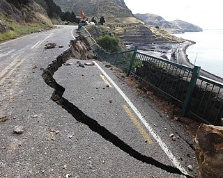Part of a road between Lyttelton and Sumner is damaged by Tuesday's earthquake on the outskirts of Christchurch, New Zealand, Thursday, Feb. 24, 2011. The magnitude-6.3 temblor collapsed buildings, caused extensive other damage and killed dozens of people in the city.