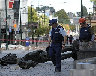 Two police officers walk past a fallen statue in Christchurch, New Zealand , Thursday, Feb. 24, 2011 while doing a patrol  after the city was hit by a 6.3 magnitude earthquake on Tuesday.  Hundreds of troops, police and emergency workers raced against time and aftershocks that threatened to collapse more buildings. They picked gingerly through the ruins, poking heat-seeking cameras into gaps between tumbles of bricks and sending sniffer dogs over concrete slabs.