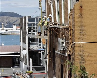 Workers clear debris of a building damaged by an earthquake in Lyttelton on the outskirts of Christchurch, New Zealand, Thursday, Feb. 24, 2011. Tuesday's magnitude-6.3 temblor collapsed buildings, caused extensive other damage and killed dozens of people in the city.