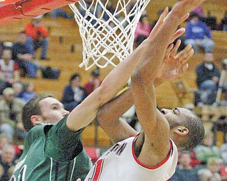 Youngstown State's Damian Eargle (21) shoots over Alec Brown of Green Bay in fi rst-half action of Thursday's Horizon League contest at YSU's Beeghly Center. Eagle posted 19 points and seven rebounds for the Penguins, who came up short against the Phoenix, 71-60.