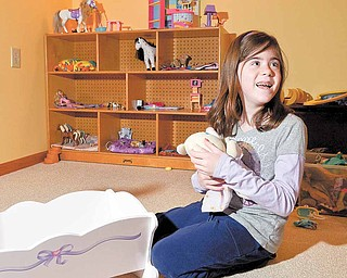 Nicole Barber, a third-grader at Springfield Local Elementary School, plays with one of her favorite toys in her room at her New Middletown home. Nicole, born with spina bifida, was saved from symptoms of severe spina bifida by fetal surgery she and her mother, Lorie, underwent nine years ago.