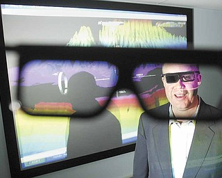 Brad Shellito, geography professor at Youngstown State University, dons 3-D glasss while demonstrating the geography department's new GeoWall 3D projection system inside the Phelps building on campus.