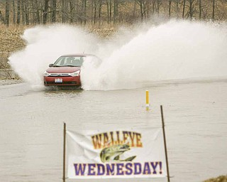 SURFS UP and Walleye Wednesday can't be far behind as a motorist blows through the water covering the road by Drakes Landing on Western Reserve Road.