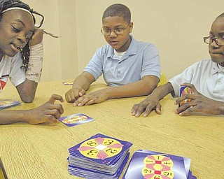 From left, Rayen Early College math students, Jah-Nice Berry and Jordan Rawl, both seventh-graders, and Carlos Hall, a sixth-grader, play a math game called Challenge 24.