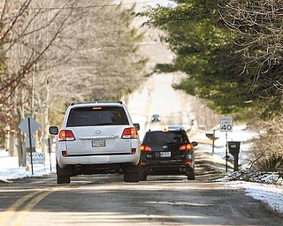 Drivers on Walker Mill Road in Boardman Township slow to a crawl as they maneuver to avoid hitting potholes.
